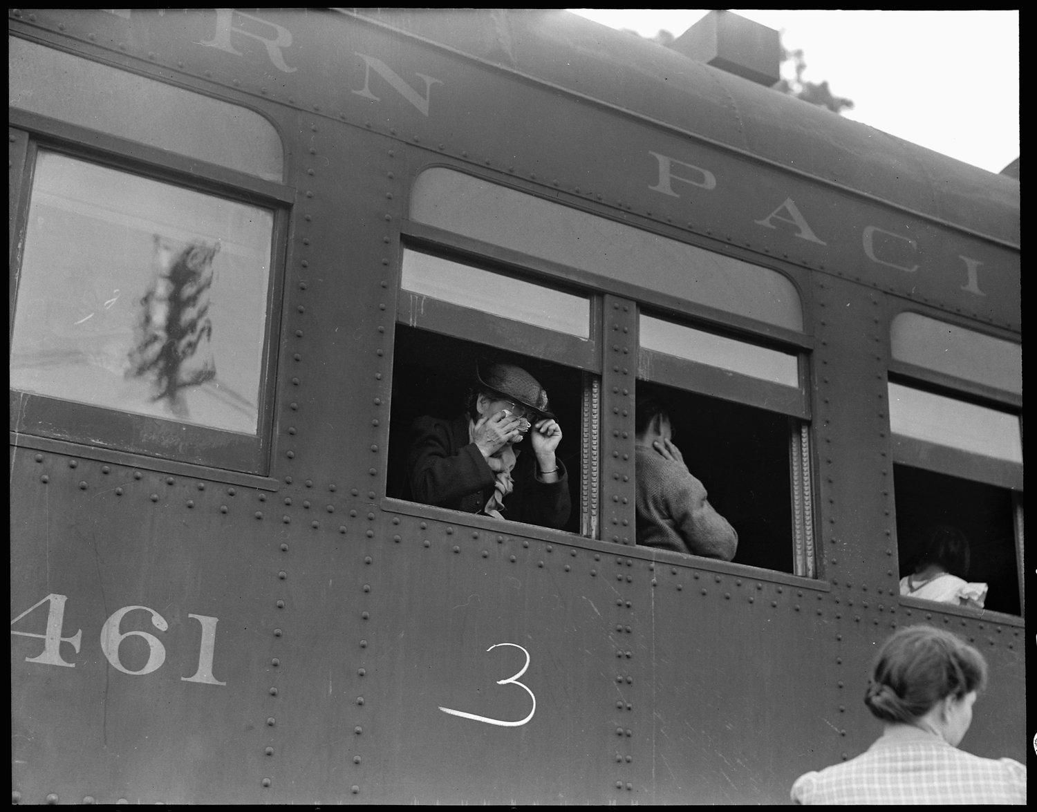 Woodland, Yolo County, California. Ten cars of evacuees of Japanese ancestry are now aboard and the doors are closed. Their Caucasian friends and the staff of the Wartime Civil Control Administration stations are watching the departure from the platform. Evacuees are leaving their homes and ranches, in a rich agricultural district, bound for Merced Assembly Center about 125 miles away.
