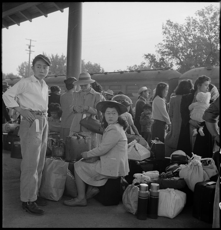 Woodland, California. Families of Japanese ancestry with their baggage at railroad station awaiting the arrival of special train which will take them to the Merced Assembly center, 125 miles away.