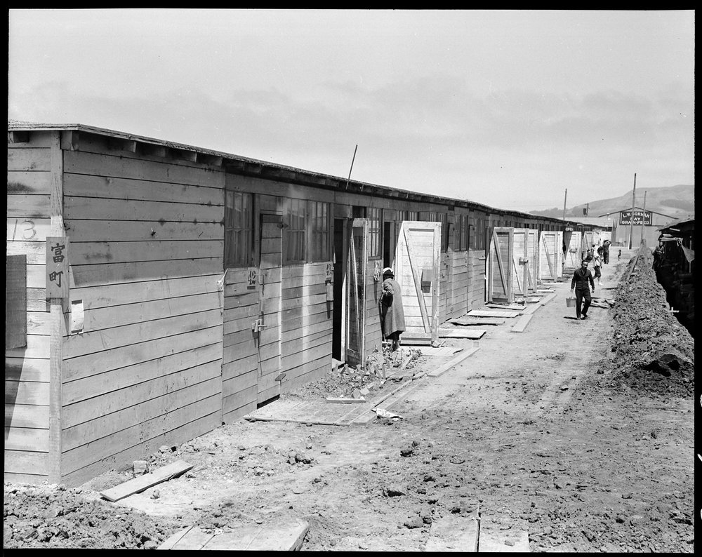 San Bruno, California. This scene shows one type of barracks for family use. These were formerly the stalls for race horses. Each family is assigned to two small rooms, the inner one, of which, has no outside door nor window. The center has been in operation about six weeks and 8,000 persons of Japanese ancestry are now assembled here.