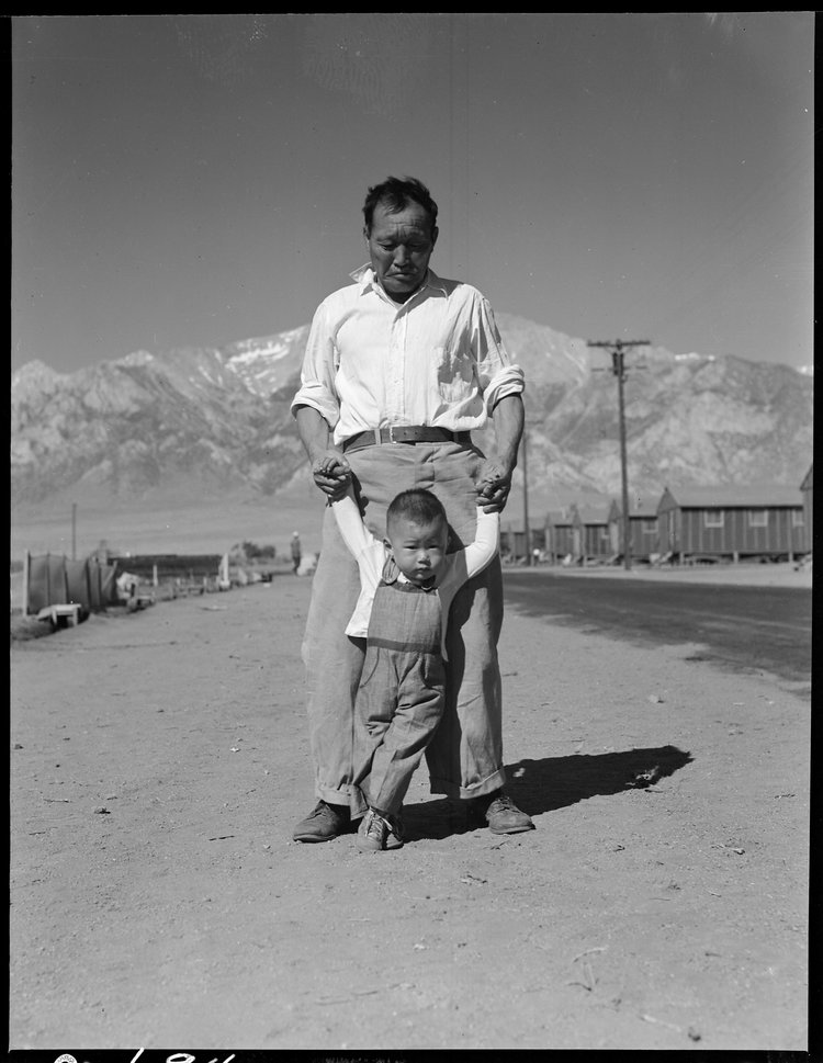 Manzanar Relocation Center, Manzanar, California. Grandfather of Japanese ancestry teaching his little grandson to walk at this War Relocation Authority center for evacuees.