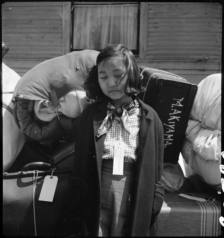 Oakland, California. Kimiko Kitagaki, young evacuee guarding the family baggage prior to departure by bus in one half hour to Tanforan Assembly center. Her father was, until evacuation, in the cleaning and dyeing business.