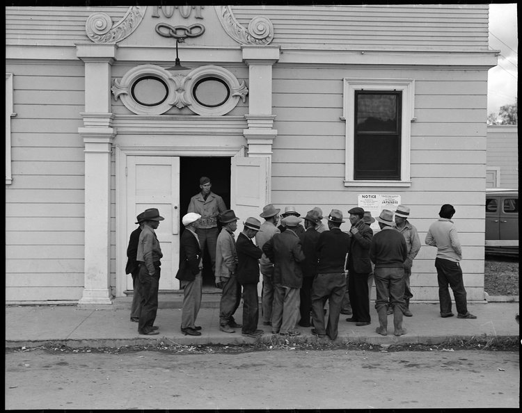 Byron, California. Field laborers of Japanese ancestry from a large delta ranch have assembled at Wartime Civil Control Administration station to receive instructions for evacuation which is to be effective in three days under Civilian Exclusion Order Number 24. They are arguing together about whether or not they should return to the ranch to work for the remaining five days or whether they shall spend that time on their personal affairs.