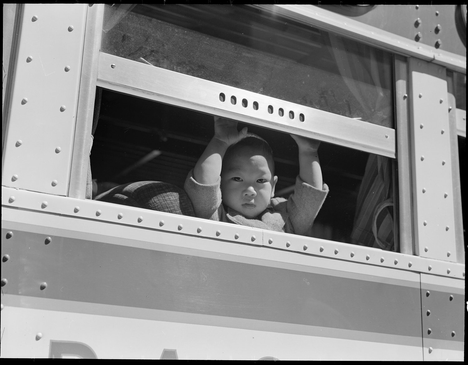 San Francisco, California. A young evacuee looks out the window of bus before it starts for Tanforan Assembly center. Evacuees will be transferred to War Relocation Authority centers for the duration.