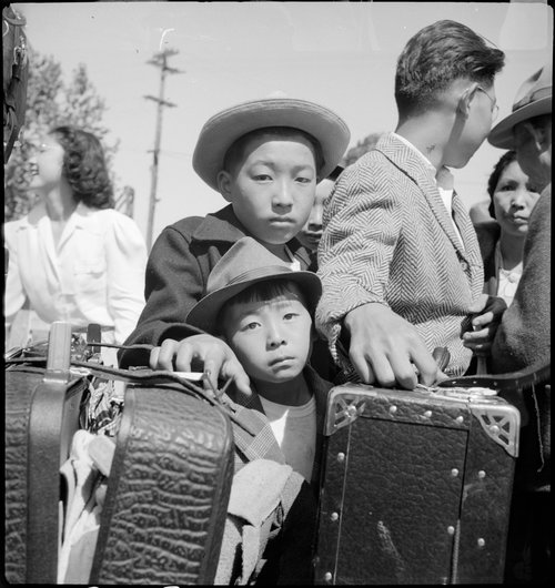 Turlock, California. These young evacuees of Japanese ancestry are awaiting their turn for baggage inspection at this Assembly center.