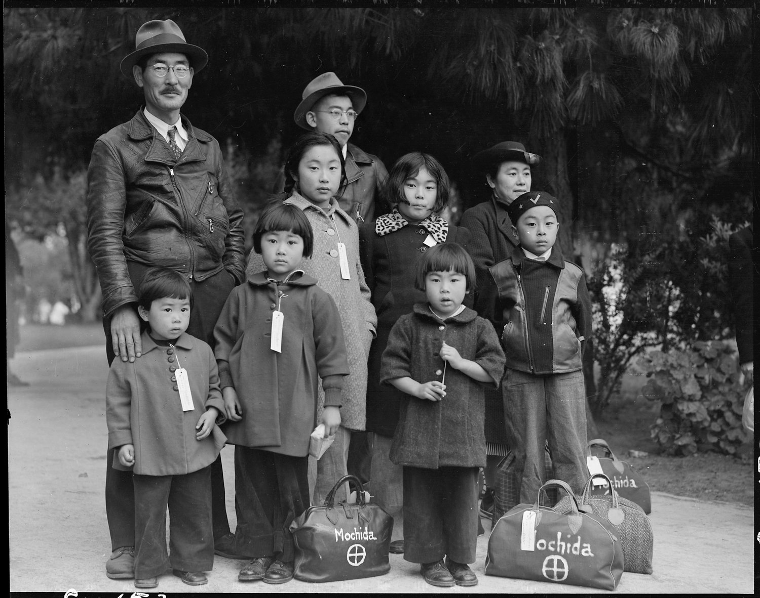 Original caption: Hayward, California. Members of the Mochida family awaiting evacuation bus. Identification tags are used to aid in keeping the family unit intact during all phases of evacuation. Mochida operated a nursery and five greenhouses on a two-acre site in Eden Township. He raised snapdragons and sweet peas. Evacuees of Japanese ancestry will be housed in War Relocation Authority centers for the duration.