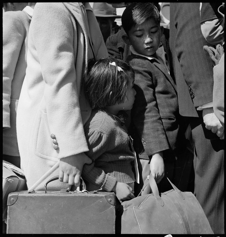 Byron, California. Third generation of American children of Japanese ancestry in crowd awaiting the arrival of the next bus which will take them from their homes to the Assembly center.