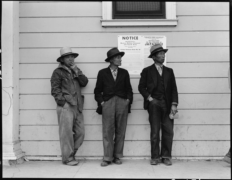 Byron, California. Field laborers of Japanese ancestry in front of Wartime Civil Control Administration station where they have come for instructions and assistance in regard to their evacuation due in three days under Civilian Exclusion Order Number 24. This order affects 850 persons in this area. The men are now waiting for the truck which will take them, with the rest of the field crew, back to the large-scale delta ranch.