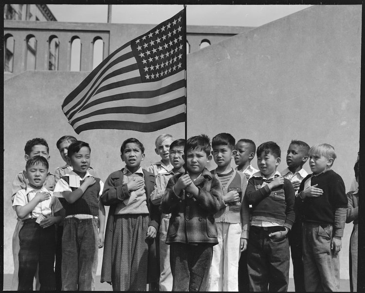 San Francisco, California. Flag of allegiance pledge at Raphael Weill Public School, Geary and Buchanan Streets. Children in families of Japanese ancestry were evacuated with their parents and will be housed for the duration in War Relocation Authority centers where facilities will be provided for them to continue their education.
