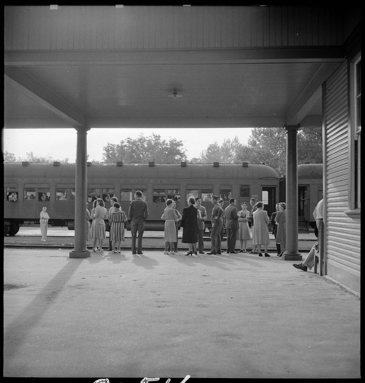 Woodland, California. This staff of Wartime Civil Control Administration workers have completed their job and stand on the platform awaiting the departure of the special train which has been loaded with evacuees of Japanese ancestry bound for the Merced Assembly center, 125 miles away.