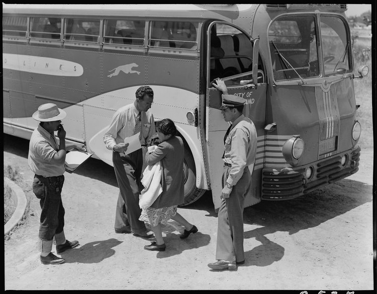 Stockton, California. Young mother of Japanese ancestry has just arrived at this Assembly center with her baby and she is the last to leave the bus. Her identification number is being checked and she will then be directed to her place in the barracks after preliminary medical examination.