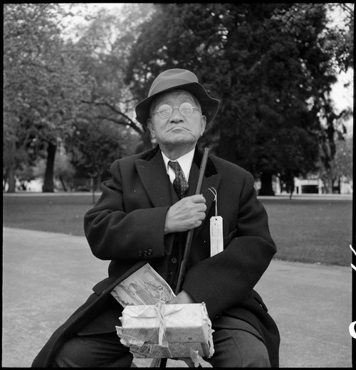 Hayward, California. Grandfather of Japanese ancestry waiting at local park for the arrival of evacuation bus which will take him and other evacuees to the Tanforan Assembly center. He was engaged in the Cleaning and Dyeing business in Hayward for many years.