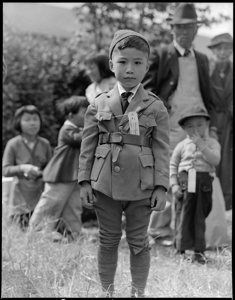 Centerville, California. This youngster is awaiting evacuation bus. Evacuees of Japanese ancestry will be housed in War Relocation Authority centers for the duration.