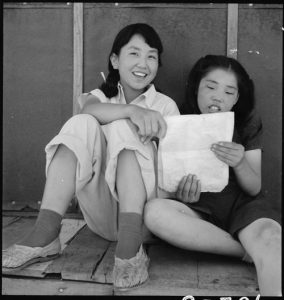 Manzanar Relocation Center, Manzanar, California. Evacuee girls practicing the songs they learned in school prior to evacuation to this War Relocaction Authority center for evacuees of Japanese ancestry.
