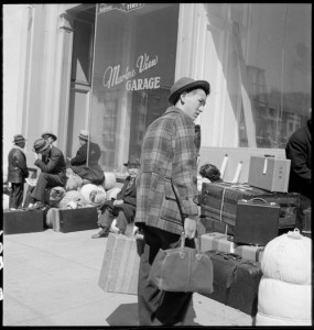 San Francisco, California. A young evacuee arrives at 2020 Van Ness Avenue, meeting place of first contingent to be removed from San Francisco to Santa Anita Park Assembly center at Arcadia, California. Evacuees will be transferred to War Relocation Authority centers for the duration.