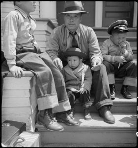 Oakland, California. Residents of Japanese ancestry waiting for evacuation buses which will take them to the Tanforan Assembly center under Civilian Exclusion Order Number 28.