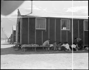 Manzanar Relocation Center, Manzanar, California. Evacuees at this War Relocation Authority center relaxing in the shade of their barrack apartment.