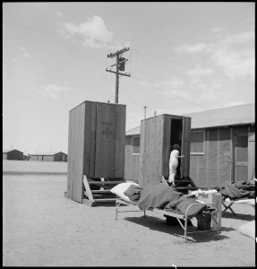 Manzanar Relocation Center, Manzanar, California. Hospital latrines, for patients, between the barracks, which serve temporarily as wards. For the first three months of occupancy medical facilities have been meager but the new hospital fully equipped, is almost ready for occupancy.