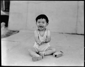 Manzanar Relocation Center, Manzanar, California. Little evacuee of Japanese ancestry in a happy mood at this War Relocation Authority center.