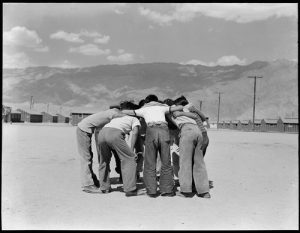 Manzanar Relocation Center, Manzanar, California. Baseball players in a huddle. This game is very popular with 80 teams having been formed to date. Most of the playing is done in the wide firebreak between blocks of barracks.