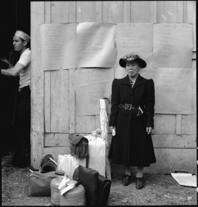Centerville, California. This evacuee stands by her baggage as she waits for evacuation bus. Evacuees of Japanese ancestry will be housed in War Relocation Authority centers for the duration.